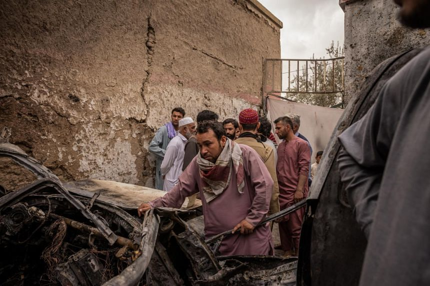 A relative examines a vehicle destroyed by a US drone strike in Kabul, on Aug 30, 2021.
