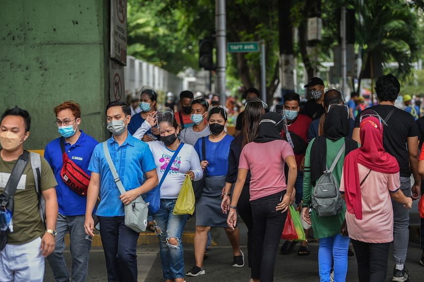 People cross a street in Manila on Sept 7, 2021.