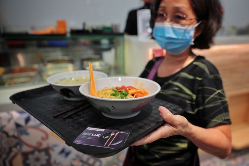 Beneficiary Tan Teck Huay with her meal at Encik Tan in Marina Square, bought using the new card funded by The Food Bank Singapore.