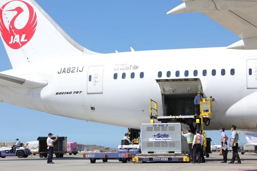 Taiwanese workers unload AstraZeneca vaccines shipped from Japan, on July 8, 2021.