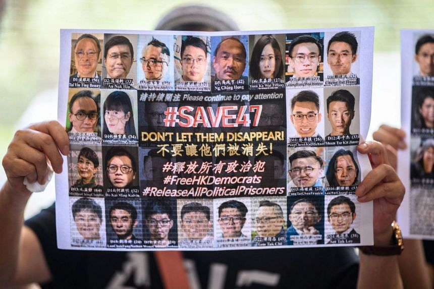 A protester holding up a poster showing some of the 47 activists, at the West Kowloon Court in Hong Kong on July 8, 2021.