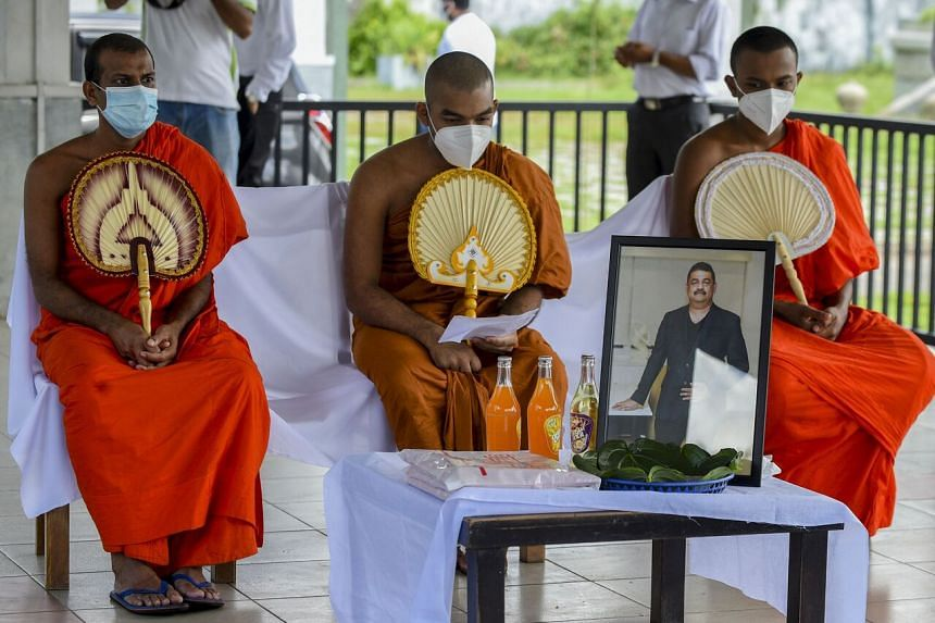 Buddhist monks performing the last rites during the funeral of Mr Eliyantha White on Sept 23, 2021.