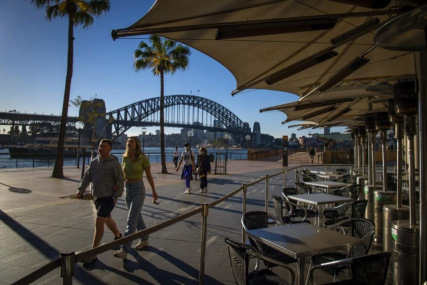 Residents passing an empty cafe near the Opera House in Sydney on Aug 13, 2021.
