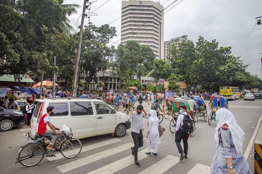 Bangladeshi people cross a road at the Mirpur area in Dhaka, Bangladesh on Sept 19, 2021.
