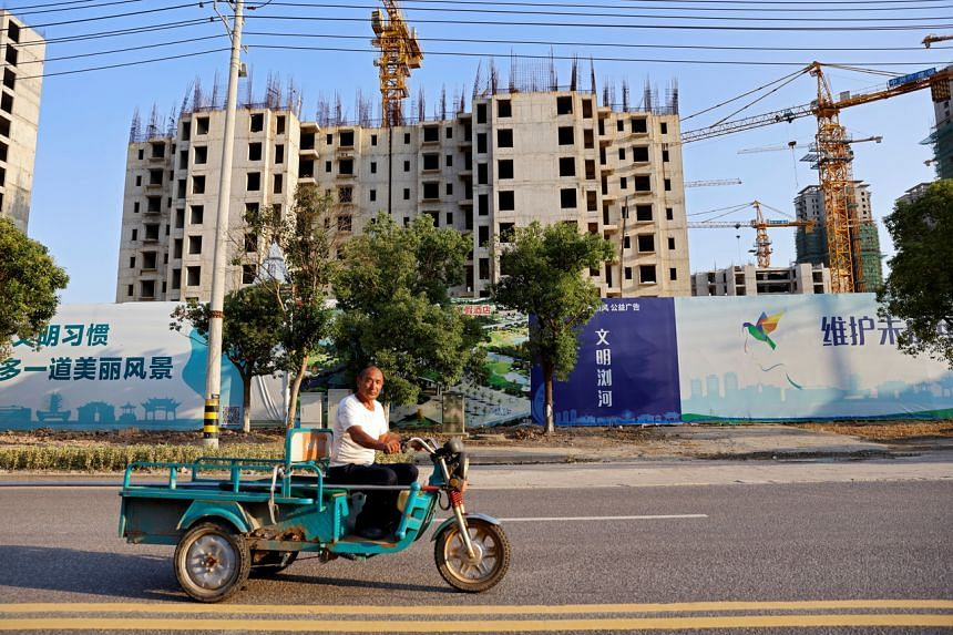 A man rides a vehicle past the construction site of Evergrande Cultural Tourism City in Suzhou, on Sept 23, 2021.
