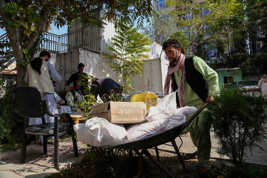 Afghans receive food aid distributed by Red Crescent in Kabul, on Sept 20, 2021.