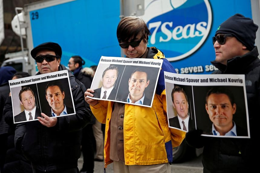 People hold placards calling for China to release Michael Spavor and Michael Kovrig at the B.C. Supreme Court in Vancouver on March 6, 2019.