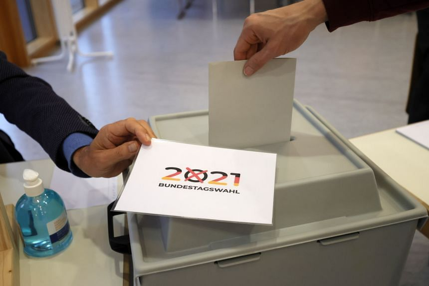 A voter casts the ballot into a box at a polling station in Gutach, Germany, on Sept 26, 2021.