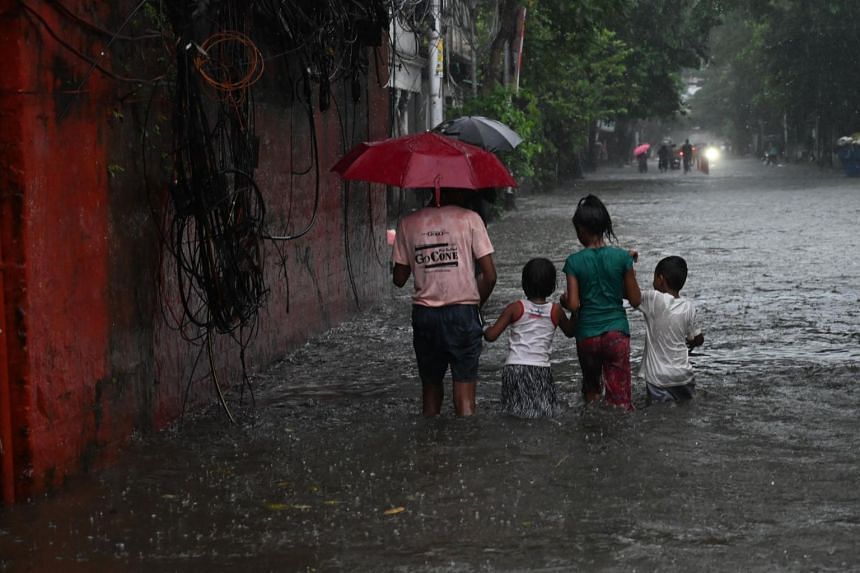 Children wade through a waterlogged street after heavy rainfall in Kolkata on Sept 20, 2021.