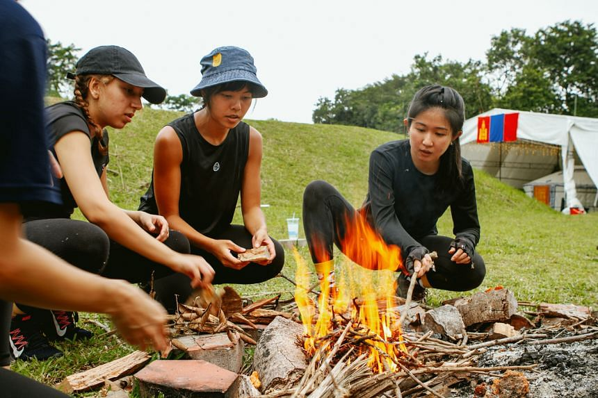 Journalist Clara Lock (right) learns survival skills such as how to start a fire without matches at a wilderness camp run by Beyond Expeditions.