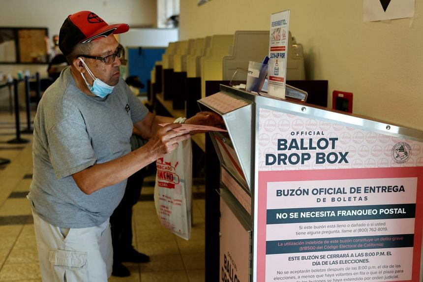 A voter drops off a mail-in ballot during the gubernatorial recall election in Sacramento, California, on Sept 14, 2021.
