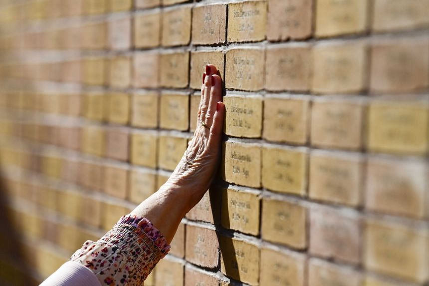 A woman places her hand at the Holocaust Memorial of Names in Amsterdam. Time is running out for prosecutors seeking to bring former members of the SS to justice as the war-time generation disappears.