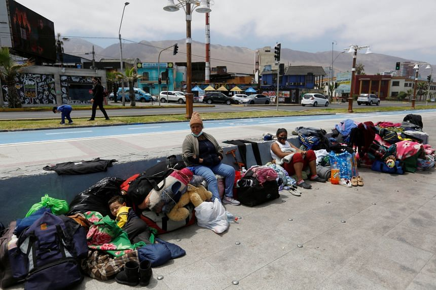 Venezuelan migrants sit along a street after their camp was destroyed during violent anti-immigration protests, in Iquique, Chile, on Sept 27, 2021.