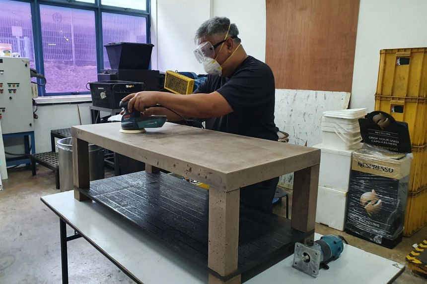 A1 Environment technical director Mohamad Ismail Ibrahim working on a table made of used coffee grounds.