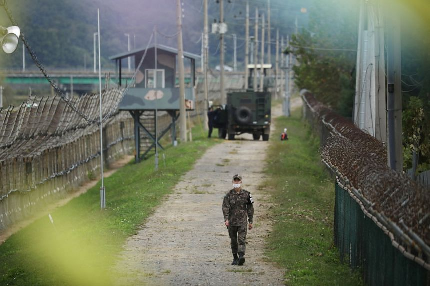 A South Korean soldier walks along a military fence near the demilitarised zone in Paju, South Korea, on Sept 28, 2021.