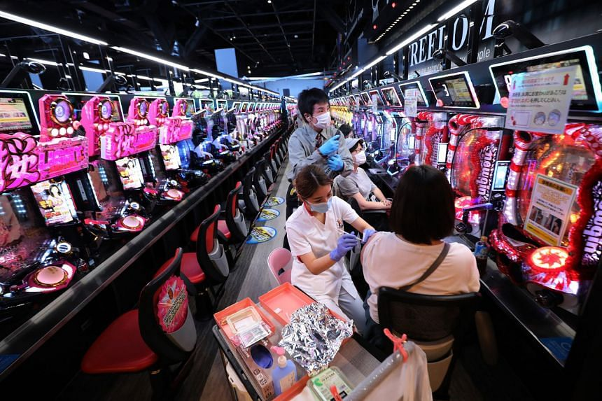 In this photo taken on Sept 14, 2021, a person is inoculated the Covid-19 vaccine at a Pachinko arcade in Osaka.