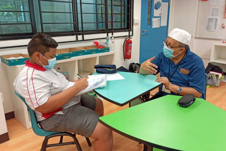Volunteer Morni Sulaiman (right) interacts with a student at Naval Base Primary School as part of RSVP Singapore's mentoring programme.