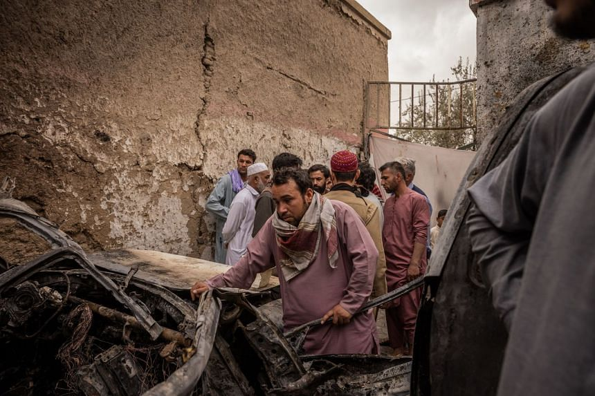 A relative views a vehicle destroyed in an American drone strike that killed 10 people in Kabul, Afghanistan, on Aug 30, 2021.