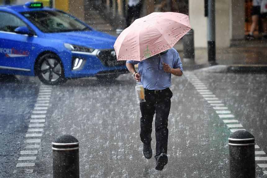 A pedestrian caught in a heavy rain at Chinatown on Sept 27, 2021.