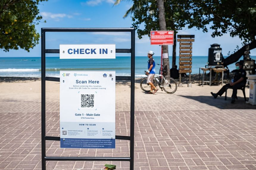A sign recommending the use of a surveillance app at the entrance of a beach in Kuta, Bali, on Sept 28, 2021.