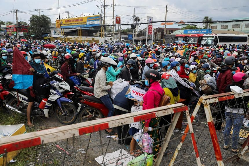 People, many of whom are migrant workers, waiting at a checkpoint to leave Ho Chi Minh city for their hometowns, on Oct 1, 2021.