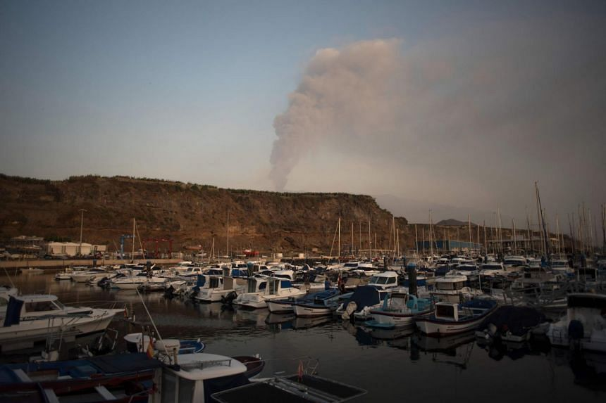 Small boats moored in the port of Tazacorte as the Cumbre Vieja volcano spews lava, ash and smoke, on the Canary Island of La Palma on Oct 3, 2021.