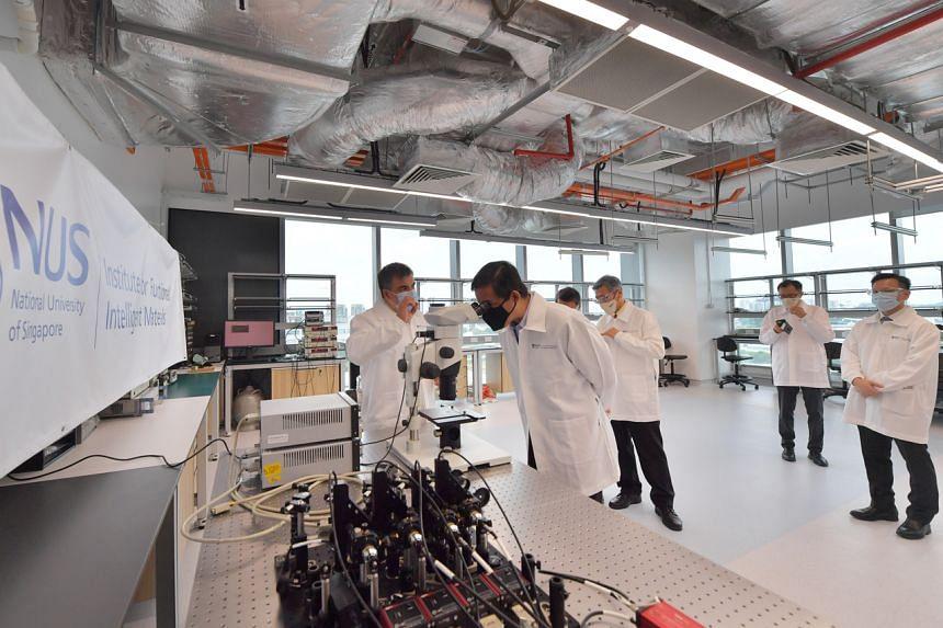 Professor Konstantin Novoselov (far left) showing Mr Chan Chun Sing (at the microscope) around one of the new laboratories on Oct 7, 2021.