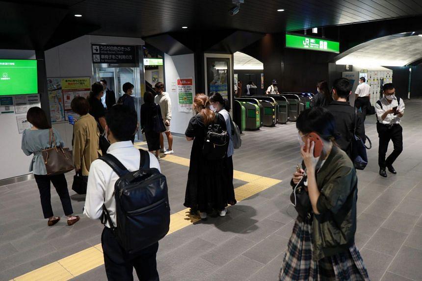 People gather at a station as train services are suspended following an earthquake in Tokyo.