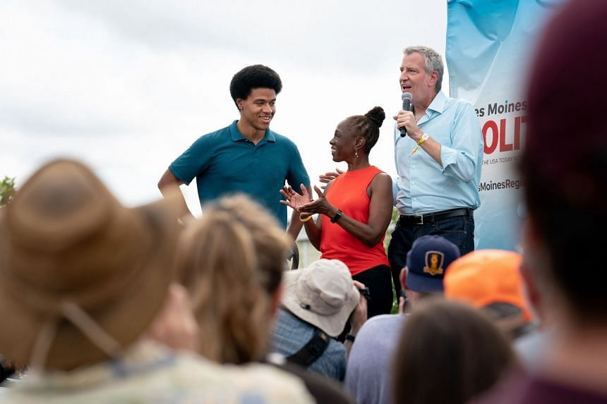 A 2019 photo shows New York City Mayor Bill de Blasio speaking at an event in Iowa, with wife Charlene McCray and his son, Dante.