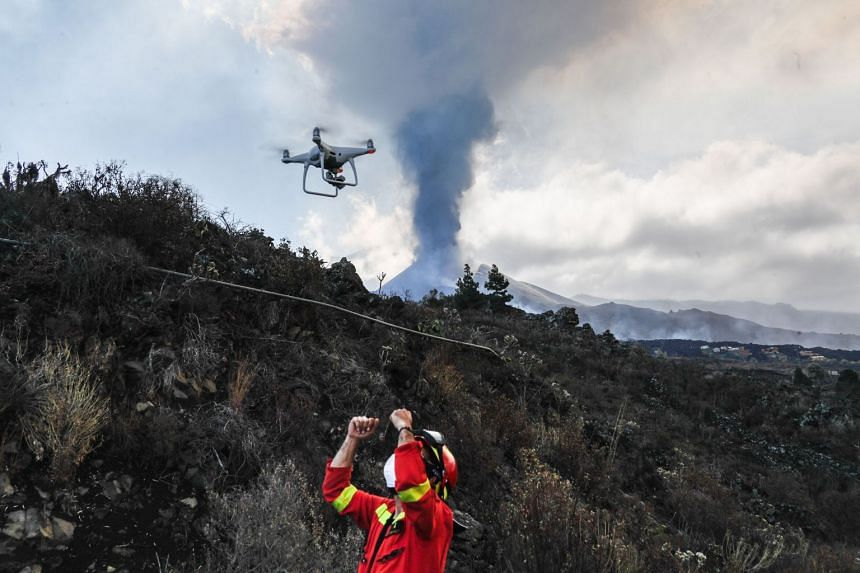 A drone is used to monitor lava flow at the Cumbre Vieja volcano pictured in the background, on the Canary island of La Palma.