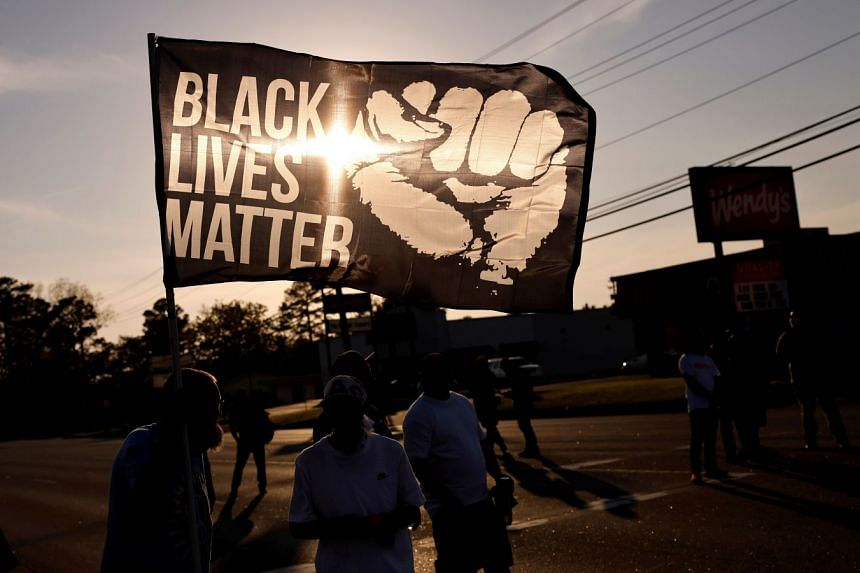 People protest over another shooting by police officers in the US under a Black Lives Matter banner.