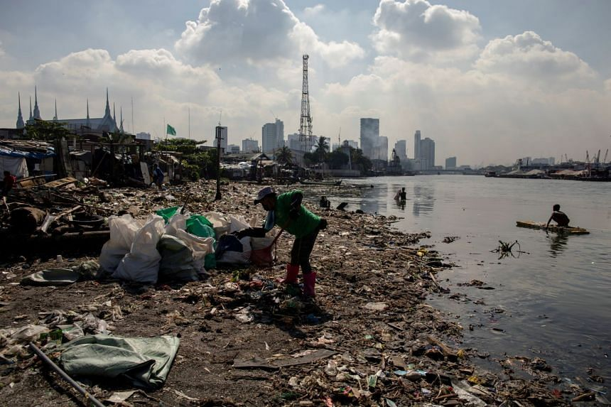 Angelita Imperio, a member of River Warriors, rakes through washed up trash from the heavily polluted Pasig River, in Manila, Philippines, in June 2021.