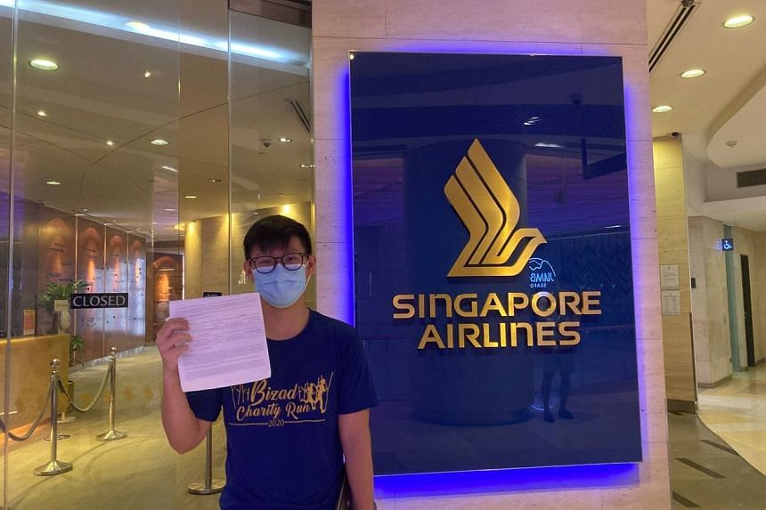 Mr Ryon Chan holding an acknowledgment slip for four premium economy tickets to Los Angeles at the Singapore Airlines service centre in Ion Orchard on Oct 9, 2021.
