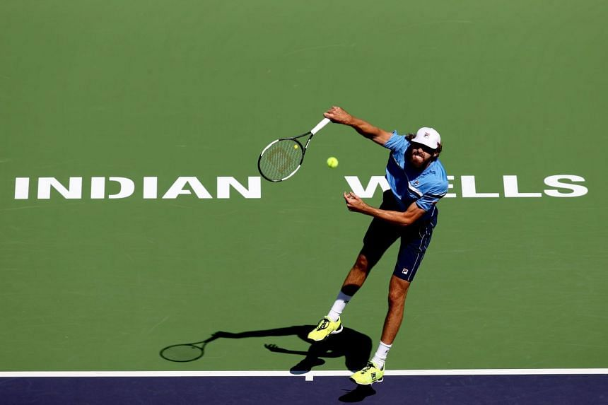 Reilly Opelka serves to Taro Daniel of Japan during the BNP Paribas Open in Indian Wells.