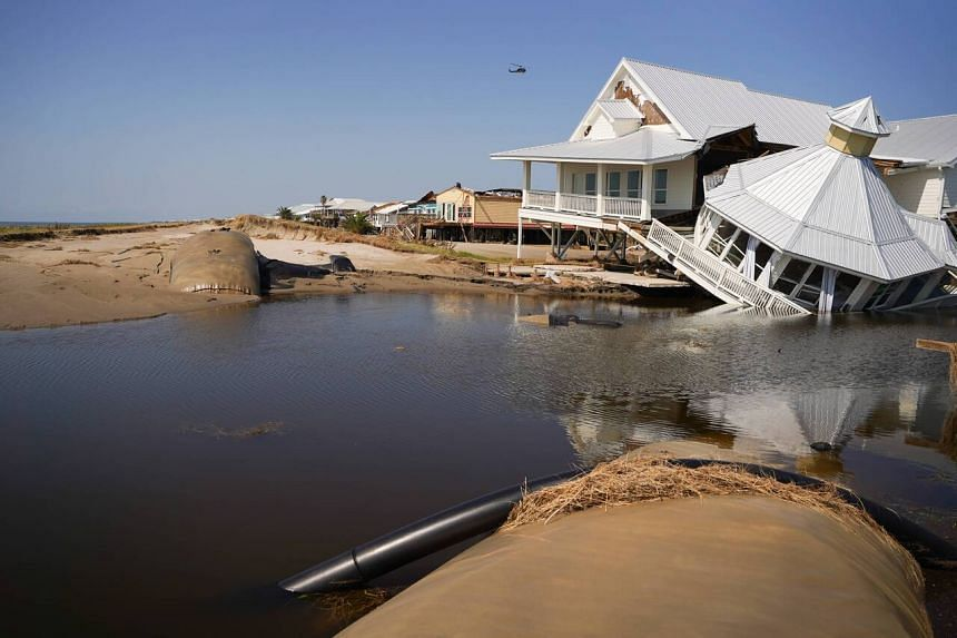 A storm-damaged house at a busted levee on the beach after Hurricane Ida swept through early last month in Grand Isle, Louisiana.