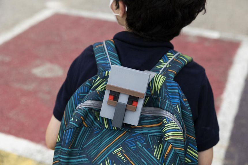 Luke Beauregard walks home from school with the CO2 monitor his mother, Lizzie Rothwell, uses to keep an eye on the school's ventilation, in Philadelphia, Oct 6, 2021.