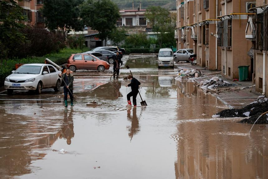 Villagers clear floodwaters near residential houses following heavy rainfall in Yitang county, Jiexiu, China's northern Shanxi province, on Oct 10, 2021.