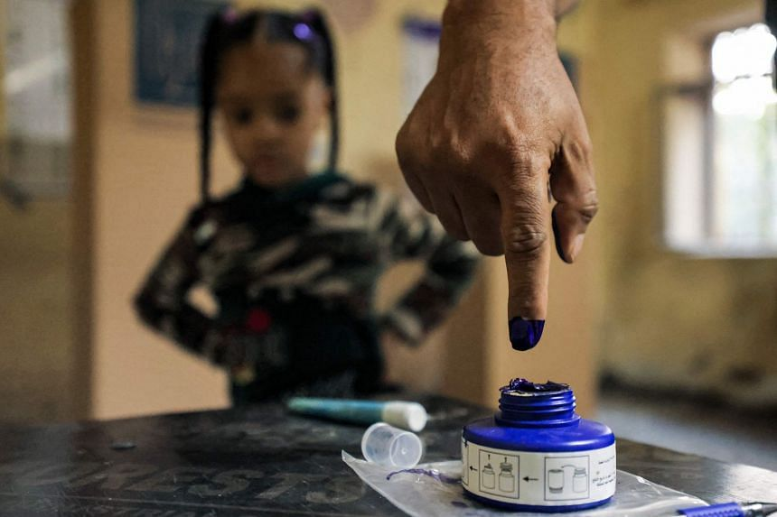 A child looks on as a man dips his finger in ink after voting at a polling station in Baghdad during the early parliamentary elections on Oct 10, 2021.