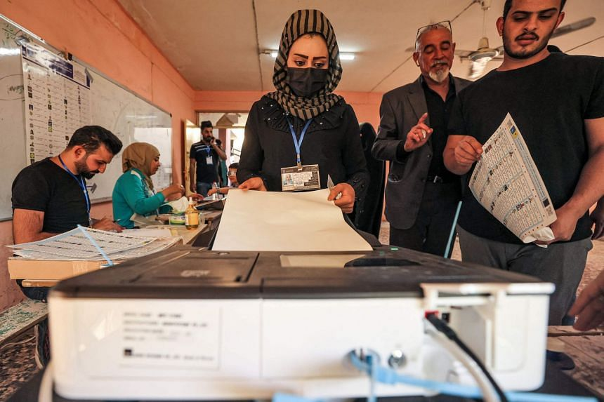A woman casts her vote at a polling station in Baghdad during the early parliamentary elections on Oct 10, 2021.