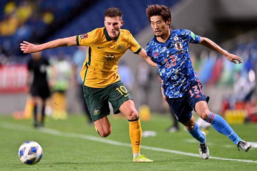 Australia's Ajdin Hrustic (left) and Japan's Hidemasa Morita during the 2022 Qatar World Cup Asian Qualifiers match, at Saitama Stadium on Oct 12, 2021.