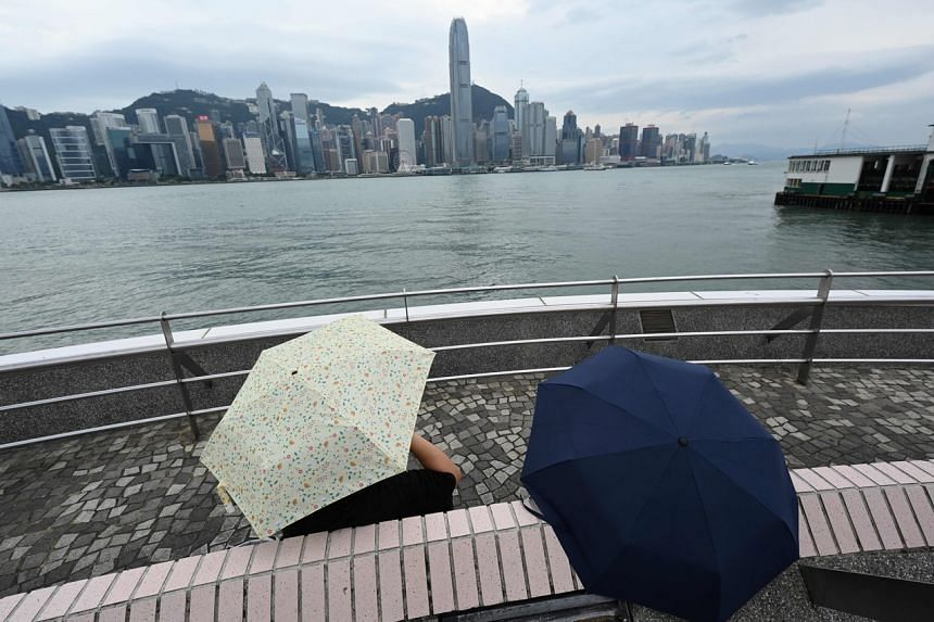 People are seen on the harbour front in Tsim Sha Tsui as the approaching Kompasu prompted forecasters to raise their alert level in Hong Kong on Oct 12, 2021.