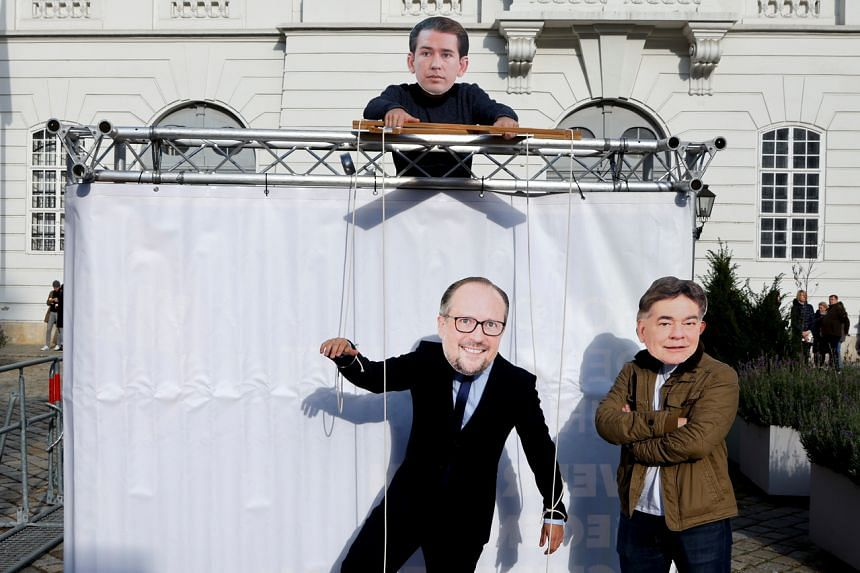Protesters wearing masks depicting Austria's Chancellor Alexander Schallenberg, Vice Chancellor Werner Kogler and former Chancellor Sebastian Kurz demonstrate outside the parliament in Vienna, Austria on Oct 12, 2021.