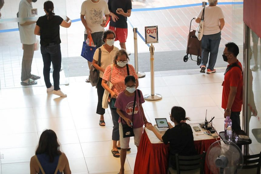 Mall patrons queueing to get their vaccination status and SafeEntry checked at the entrance of Heartland Mall on Oct 13, 2021.