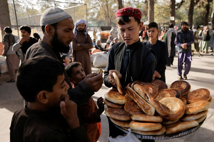A boy sells bread at a makeshift shelter for displaced Afghan families, at Shahr-e Naw park, in Kabul, Afghanistan on Oct 4, 2021.