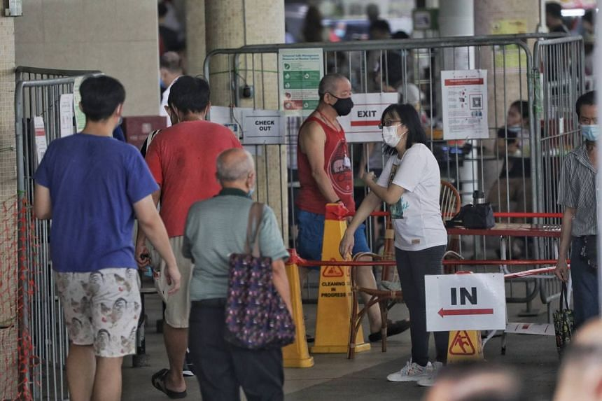 A staff manning the entry point at Bedok Interchange Hawker Centre checking the vaccination status of people on Oct 13, 2021.