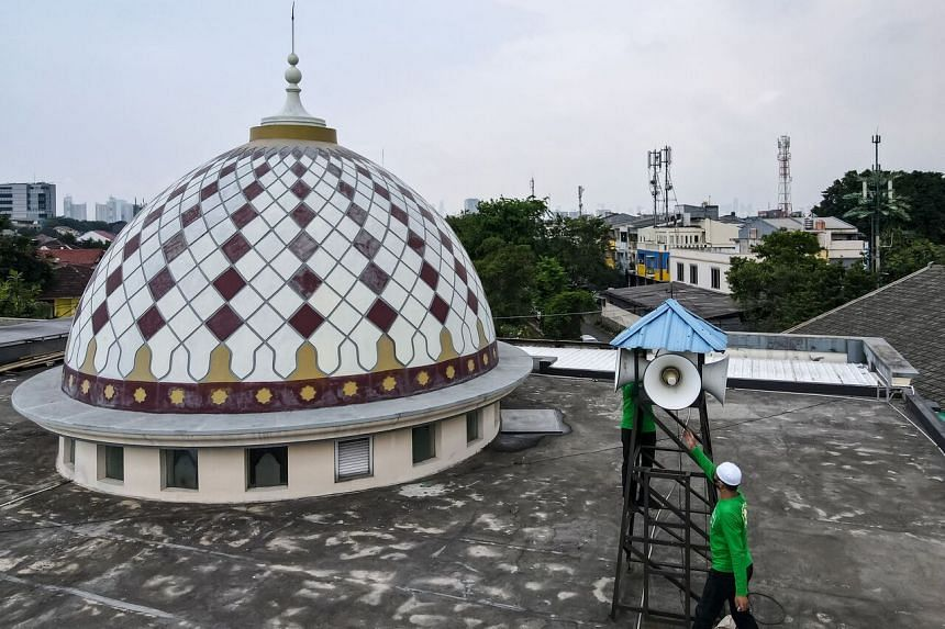 An official inspecting the mosque's speakers in Jakarta on Sept 7, 2021.