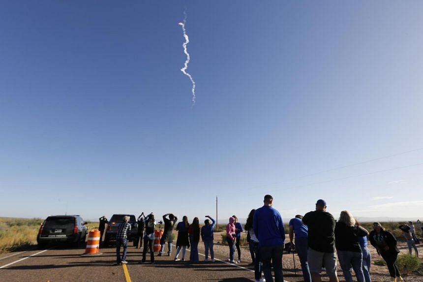 Onlookers watch as Blue Origin's New Shepard rocket blasts off near Van Horn, Texas, on Oct 13, 2021.
