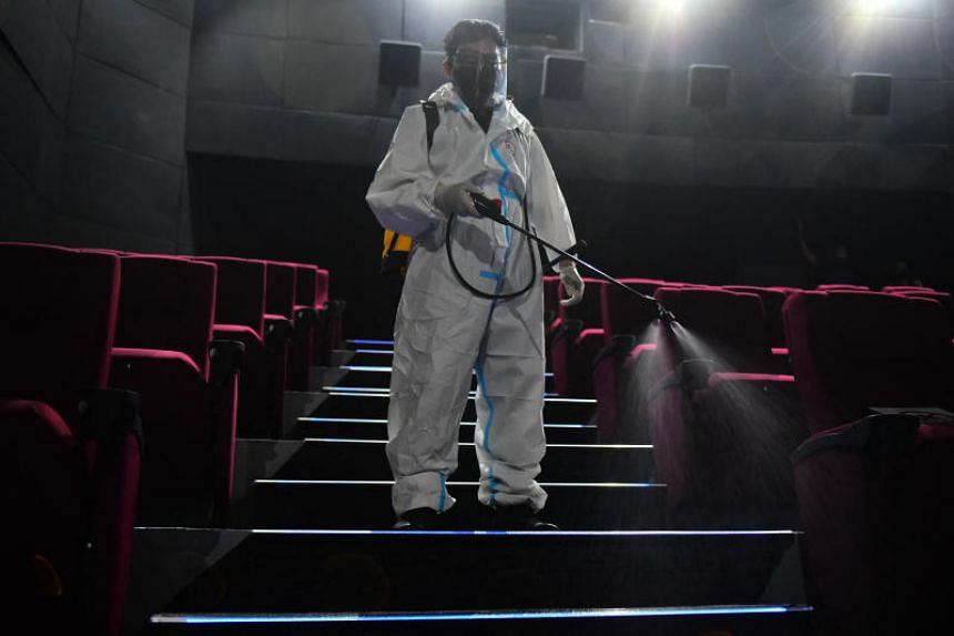 A worker in personal protective equipment sprays disinfectant inside a cinema in Manila, on Oct 14, 2021.