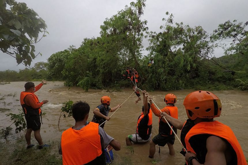 Rescuers evacuating residents from their homes near a swollen river in Cagayan province, Philippines on Oct 11, 2021.