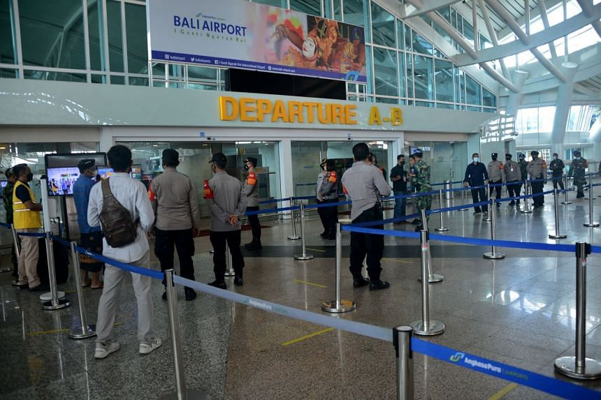 Airport officers in the international departure terminal at Ngurah Rai airport in Bali on Oct 14, 2021.